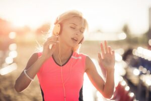 Young woman enjoying music on the beach